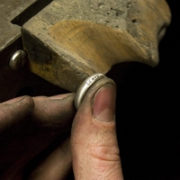 Additional diamonds being set into a ring at the request of a customer